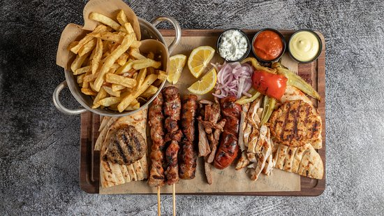 Kreatofageion: Meat Variety Platter: Chicken & pork sticks, beef & chicken burgers, grilled chicken breast, chopped grilled pork, kebab and sausage -  served with onions, grilled tomatoes & peppers, pita breads and fresh fries.
