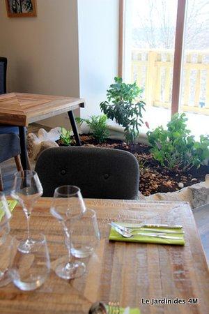 La salle de restaurant du Jardin des 4M avec une vue panoramique sur le jardin, et plus loin, la forêt et les collines de Haute-Loire et le Mont Mezenc.