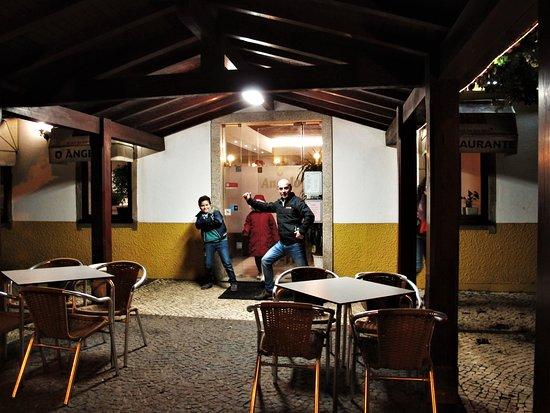 O Angelo: Terraza a la entrada del restaurante con cliente contento (al parecer)
