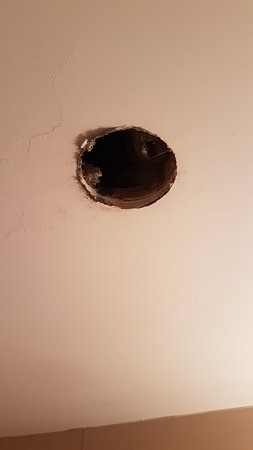 Huge hole on the bathroom ceiling, above the shower