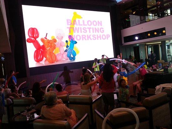 Norwegian Escape: Atrium balloon activity, c/w mega large LED screen.