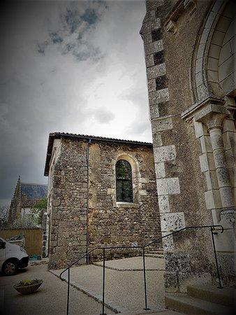 """Ménigoute possède 3 anciens lieux de culte : l'ancienne collégiale Saint-Jean-Baptiste qui devint église paroissiale en 1808, l'église primitive devenue aujourd'hui salle communale """"romane"""", et la chapelle, toutes trois alignées le long de la rue du village.   Une croix hosannière est située derrière l'église et devant le logis """"château Boucard""""."""