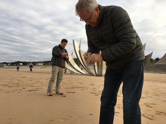Viking Kadlin: The time spent at Omaha Beach was amazing...one of our favorite shore excursions. In this picture, my husband and son-in-law gather sand from the beach. We purchased small glass containers, containing the beach name, before arriving at the beach. An inexpensive yet beautiful souvenir.