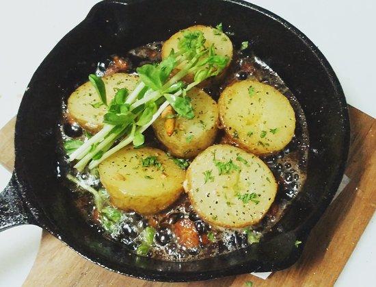 お芋のアヒージョ。北海道産のジャガイモとパンチェッタ(厚切りベーコン)を鉄の小鍋で。バターを落として直火でアツアツ!カリカリになったパンチェッタとオリーブオイルもバケットに浸して残さず召し上がれ♪