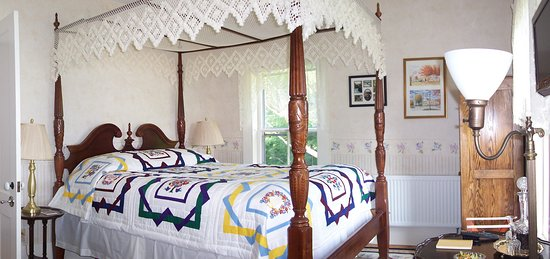 The Vermont Federal Room has a canopy queen bed, private bath with a shower, and views of the surrounding hills and mountains