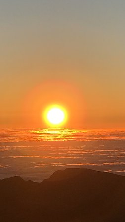The sun rising above the clouds at Haleakala Crater