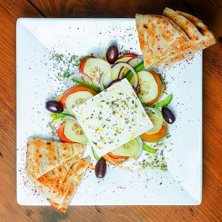 Ensalada griega: Tomate, pepino, pimiento, olivas, queso feta  y pan de pita artesanal.