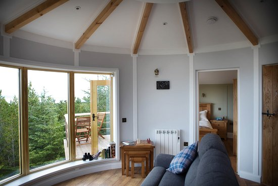 Uist Forest Retreat Ltd: Living area with large wrap around windows to watch the tide come and go on Claddach Vallay. Private balcony nestled in the trees