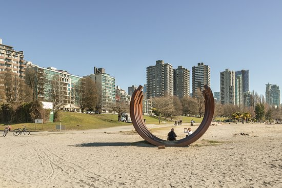 Sunset beach looking toward Beach Avenue and the where the Bernar Venet's monumental work 217.5 Arc x 13 is on display which illustrate the beauty, balance, and malleability of raw steel. The name of this artwork is a precise description of its mathematical composition. All of the beams in the sculpture are nested and curved to the same angle providing a sense of balance and grace.