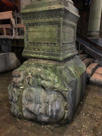 Basilica Cistern: Una de las cabezas de Medusa, rodeada de monedas de la buena suerte