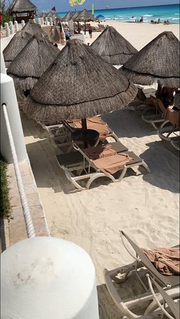 Shaded area with empty chairs under palapas - vacant for hours. Prevalent across beach area