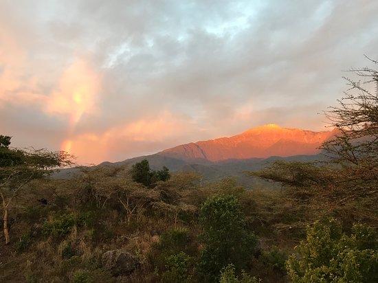 Hillside Retreat – Africa Amini Life: Blick von der Terrasse nach Süden auf den Mount Meru bei Sonnenaufgang (mit Regenbogen)