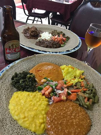 Traditional ethiopian food, many vegetables, meat over a big injera