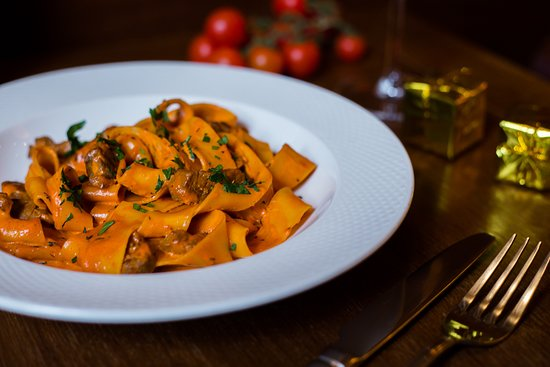 Wide ribbon pasta with chunks of beef loin in cream - tomato sauce with garlic, chilli, peppers and thyme