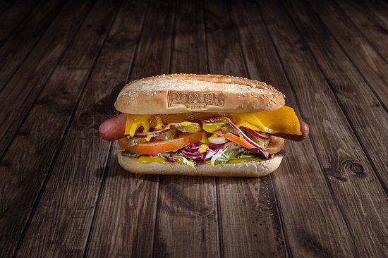 Boxer Food: Súper Perrito de la Costa Oeste: Salchica de 20cm, pepinillo, cebolla morada, queso queddar, lechuga, tomate, salsa miel y mostaza.