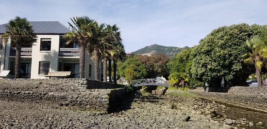 View of corner unit from water's edge, showing stream and bridge to other parts of motel