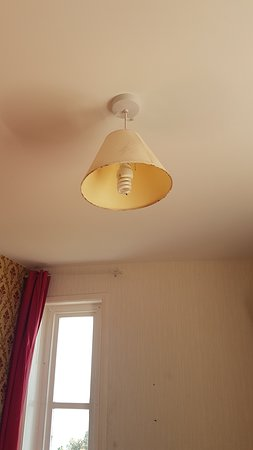 Filthy lampshade hanging above our unmade bed in our room with a seaview through that very small solid Window