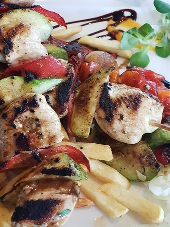 Grilled meat and vegetable skewers with French fries