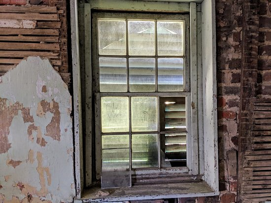 Aiken-Rhett House: Notice loose pane of glass leaning against lower corner of window.  This was how the window was found so it is left that way during preservation.