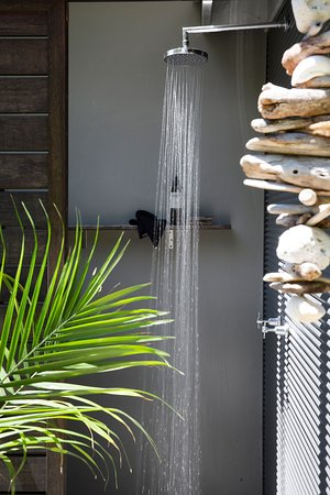 The luxe outdoor shower has hot and cold water, pebble floor, views to the trees and sliding privacy screen.