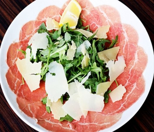 Carpaccio Aida Carpaccio (thinly sliced raw filet of beef), arugula, shaved grana padano cheese.