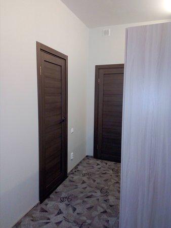 Вид из глубины номера на дверь в санузел и на входную дверь в мини-отеле Ниа-Лотте в Санкт-Петербурге. Отель в 3 минутах от Исаакиевской площади! Идеально для туристов в Санкт-Петербург.  Справа на фото - шкаф для одежды