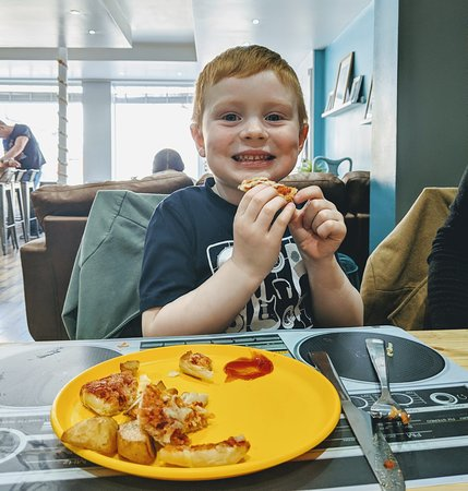 Noah enjoying his kid's stone baked pizza and twice cooked chips