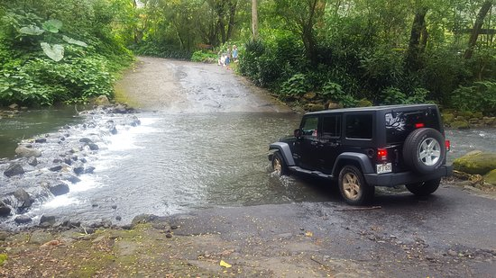 Honokaa, Havaj: Our friend's jeep entering the river. This is the road toward the falls. Only distant views of the falls, nothing up close.  County road ends about 1/4 mile where you need to turn around.