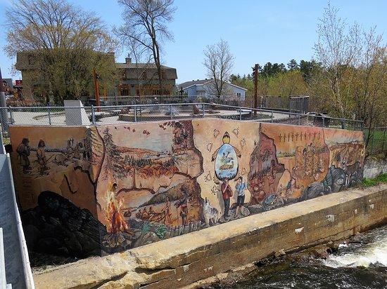 Wendake, Canada: Fresque du Peuple Wendat sur le mur bordant la place Onywahtehretsih et la rivière Akiawenrahk juste avant que celle-ci ne se jette dans les Chutes Kabir Kouba.