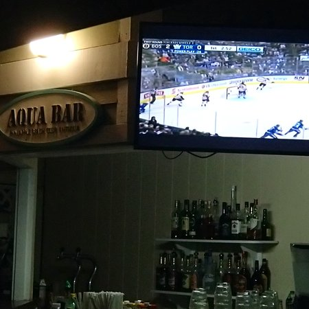 Pineapple Beach Club Antigua - All Inclusive: Watching the Hockey game at the Aqua Bar.  Must of been 25 people watching the game.  Most of us were Canadians. Too bad leafs lost. Bar was closed however Manager came out  and handed  glasses of beer to everyone.