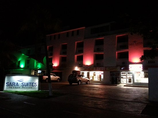 Sara Suites: Exterior by night - the Oxxo entrance is at the right