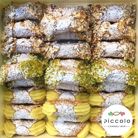 Cannoli Piped Fresh - vanilla custard, classic ricotta with pistachio and hazelnut custard dipped in chopped hazelnuts.