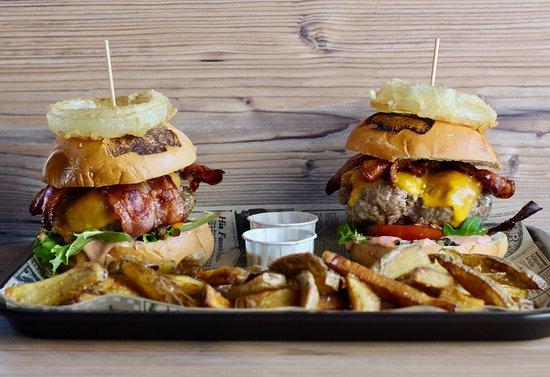 Dos hamburguesas con su ración de patatas fritas.