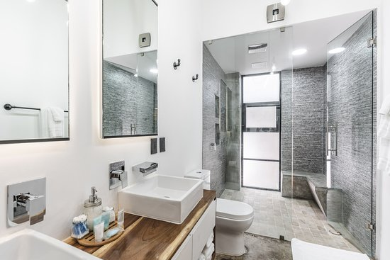 Lofts On Basilio: Loft 202 & 302 feature luxury showers with two rain shower heads, concrete bench and a double sink.