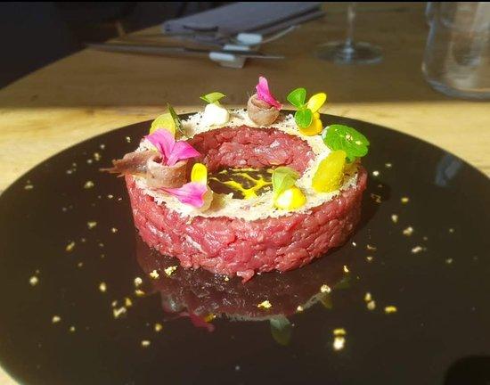 Eclissi battuta di filetto di manzo a punta di coltello, cialda al Parmigiano, gel fiori e germogli