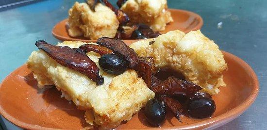 Filetto di baccalà fritto con peperoni e olive nere.