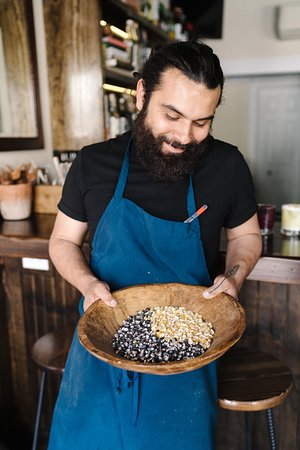 Ivan Aguilar; chef of Pink Cactus holding heirloom corn from Oaxaca. Pink Cactus nixtamalizes all the corn in house used for it's masa production.