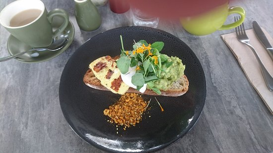 Samford, أستراليا: Broad bean and avo smash with poached egg and haloumi on seedy spelt sourdough made in house, with hazelnut dukka