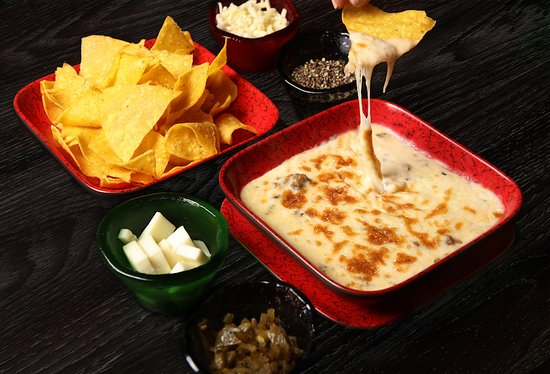Bomba Burrito: QUESO FUNDIDO HOMEMADE ARTISAN STYLE JACK CHEESE FONDUE WITH GARLICKY ROASTED PEPPERS & CHORIZO SERVED WITH CORN TORTILLA CHIPS