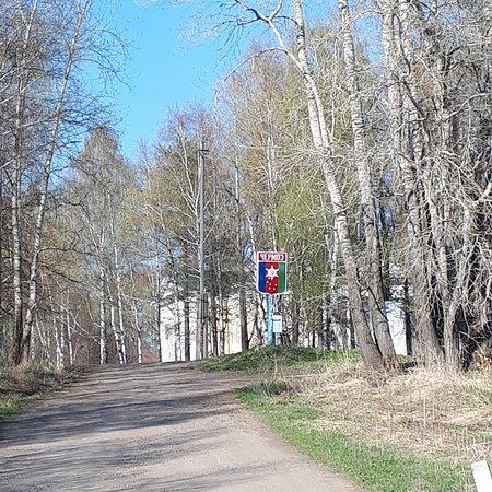 Chermoz, روسيا: Дорога от дамбы, разделяющей Чермозский пруд и Каму. Виднеется герб города Чермоз.