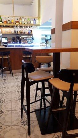Vista parcial local. Mesas altas con sillas tipo taburete