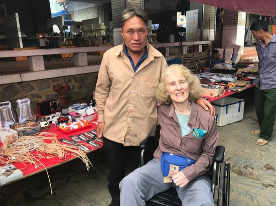 Me with a man who insisted on giving me a small amount of money due to my disability at Bac Ha Market.