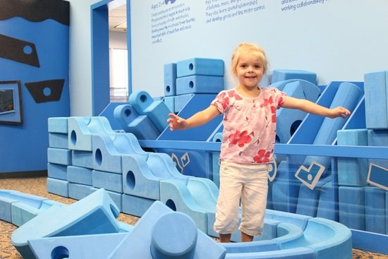 Coralville, IA: Build large-scale structures—like castles, rockets, and ramps—using big, blue Imagination Playground blocks in the Blue Room exhibit.