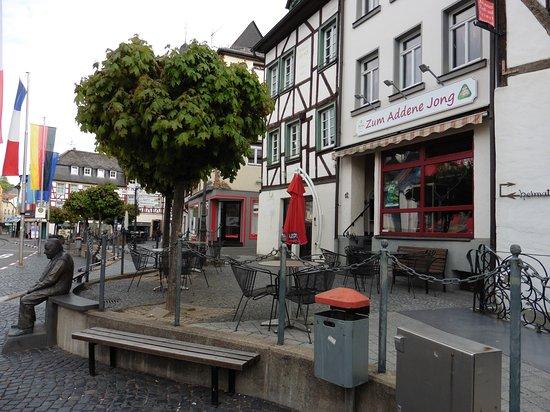 Adenau, Alemania: Blick auf Biergarten des Lokals mit Bronzefigur