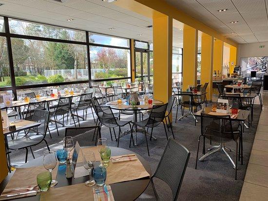 La salle de restaurant avec vue dégagée sur le parc arboré