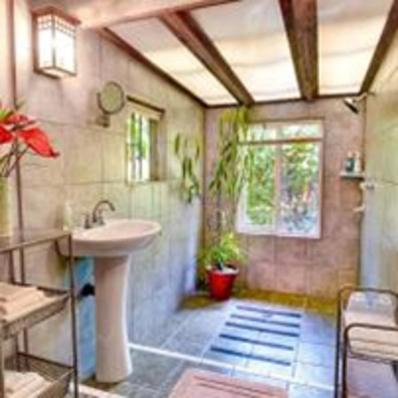 Volcano Artist Cottage's Romantic Zen Bathroom opens up to the outside private garden.
