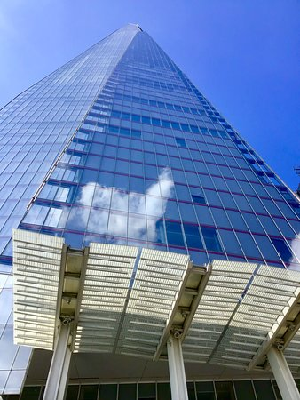 The white fluffy clouds reflected in the face of The Shard