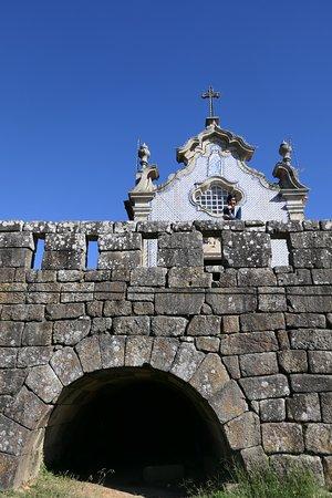 Um arco romano da ponte e parte da fachada da igreja.