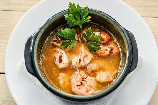 """Creveți""""Al Ajillo"""" 150 g/25 RON Creveți proaspeți, decorticați, flambați în Cognac și hidratați cu un sos iute pe bază de vin alb de """"Rioja"""" chilli, usturoi și pătrunjel proaspăt. Pâinea este inclusă."""