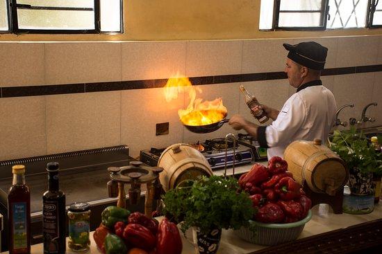 la cocina del restaurant casa de yeny y el chef juan carlos flameando camarones